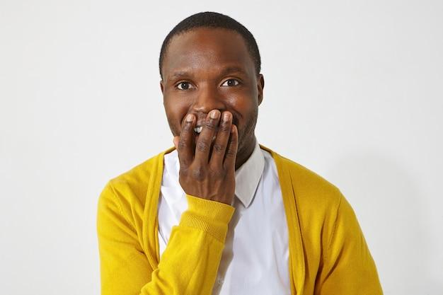Homem de pele escura feliz e animado cobrindo a boca com a mão, não consigo acreditar em notícias positivas surpreendentes. retrato de um africano atraente e emocional usando roupas elegantes e sorrindo com entusiasmo