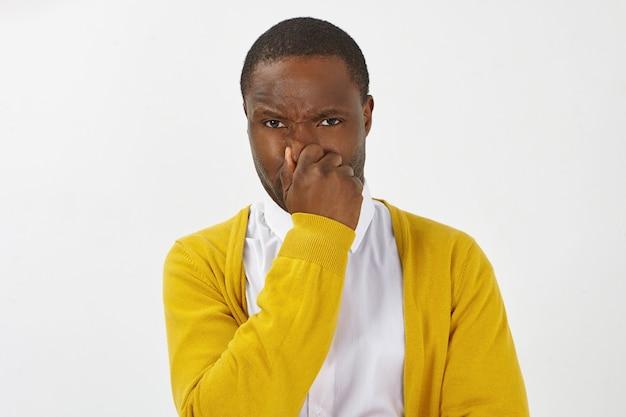 Homem de pele escura frustrado e descontente em um cardigã amarelo elegante prendendo a respiração e apertando o nariz por causa do cheiro nojento, fedor ou odor corporal de meias sujas, axilas suadas ou comida estragada