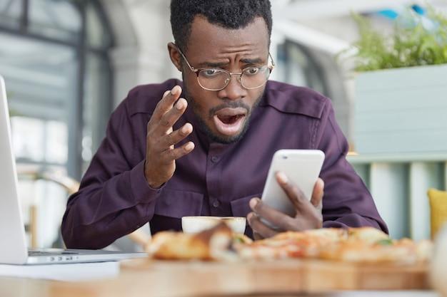 Homem de pele escura frustrado olha desesperadamente para a tela, lê informações no smartphone, senta-se em um café