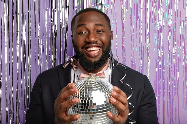 Homem de pele escura muito feliz segurando uma bola de discoteca, comemora algo na festa, usa um terno elegante, parece feliz, fica de pé sobre uma parede roxa com cortina de ouropel, tem um sorriso largo, mostra os dentes brancos