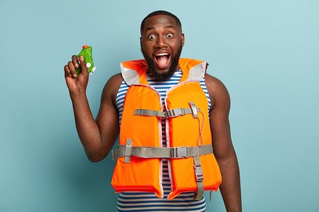 Homem de pele escura radiante brigando com água com amigos na praia, exclama feliz, usa colete salva-vidas laranja