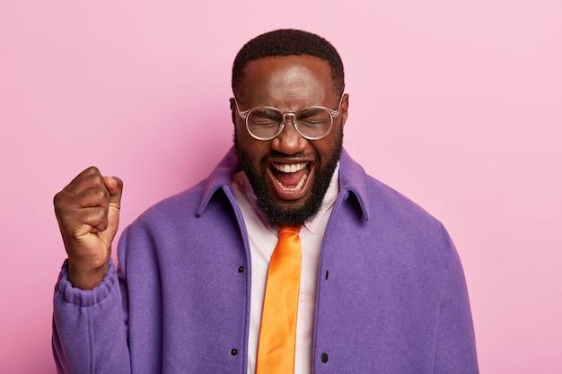 Homem de pele escura satisfeito levanta o punho cerrado, grita, sim, comemora o sucesso, usa gravata laranja, jaqueta roxa, fica de pé contra o espaço pastel