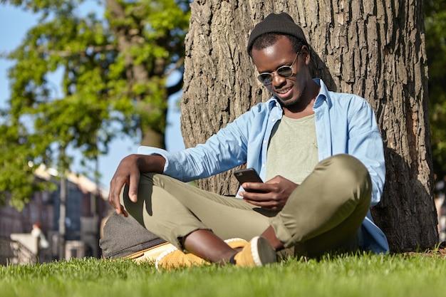 Homem de pele escura sentado na grama perto de uma árvore