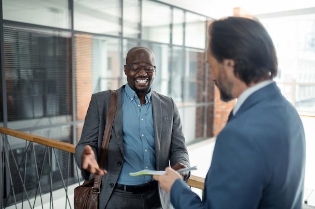 Homem de pele escura sorrindo. homem alegre de pele escura sorrindo enquanto conversava com um parceiro de negócios no escritório