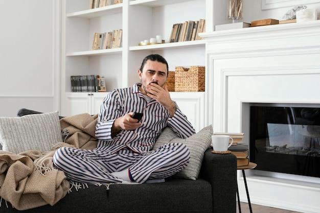 Homem de pijama assistindo tv