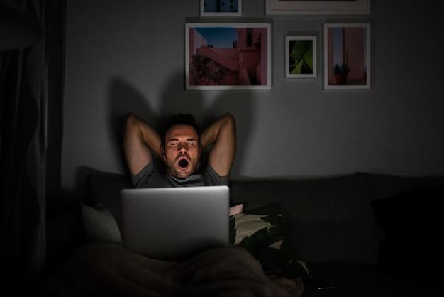 Homem de pijama com um computador bocejando
