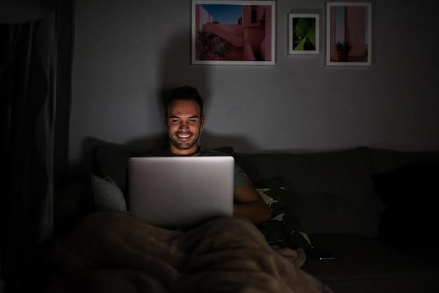 Homem de pijama com um computador