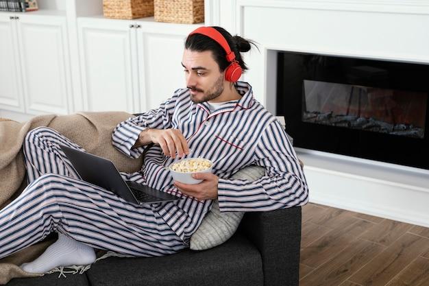 Homem de pijama comendo pipoca no alto