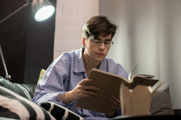 Homem de pijama lendo livro