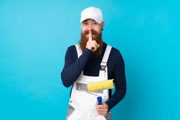 Homem de pintor com barba longa ao longo da parede azul, fazendo o gesto de silêncio