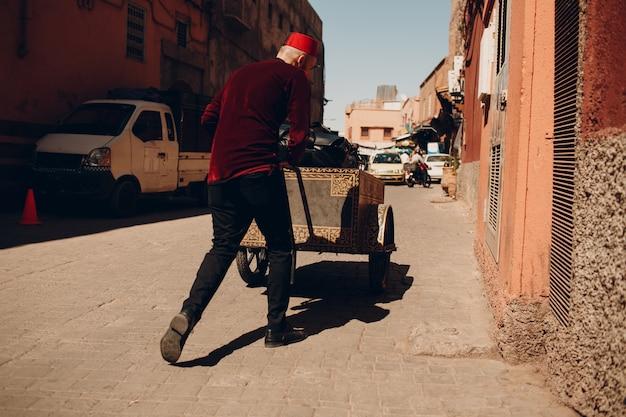 Homem de porteiro cansado com bagagem pesada de carrinho e turista andando na rua para o hotel em marraquexe, marrocos.