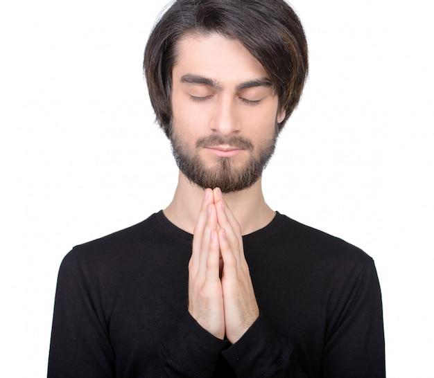 Homem de preto está rezando em um branco.