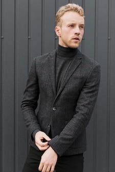 Homem de preto, organizando a manga da jaqueta