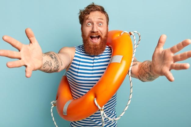 Homem de proteção amigável posando com bóia salva-vidas
