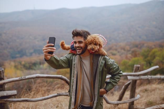Homem de raça mista atraente sorridente na capa de chuva tomando selfie com seu cachorro