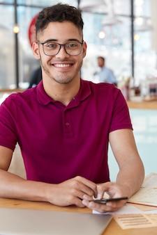 Homem de raça mista feliz com expressão facial alegre, bate-papos no celular, conectado à internet sem fio, modelos contra o interior do café, tem um sorriso, usa camiseta casual, óculos ópticos. blogging