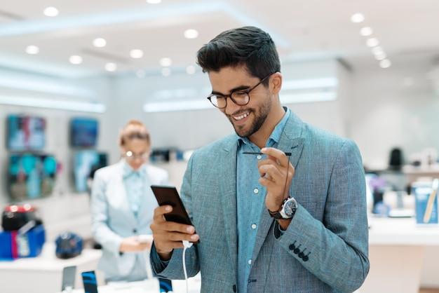 Homem de raça mista sorridente tentando novo telefone inteligente. interior da loja de tecnologia, no cliente de plano de fundo em pé perto de carrinho. interior da loja de tecnologia.