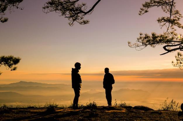 Homem de reboque silluate levantar a mão e em pé durante o pôr do sol no topo da montanha