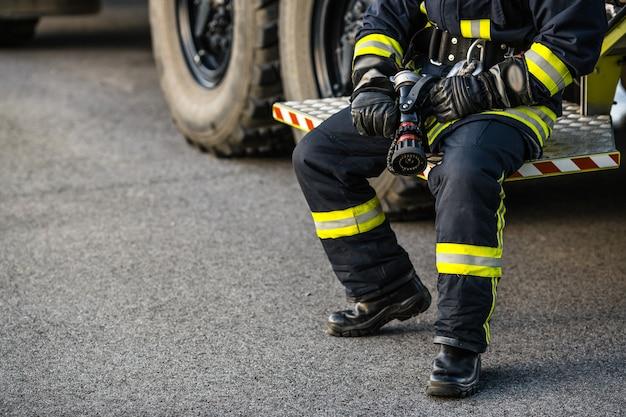 Homem de resgate de bombeiro. sapador-bombeiro no uniforme e capacete perto da viatura de incêndio.