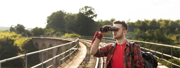 Homem de retrato com mochila olhando com binóculo