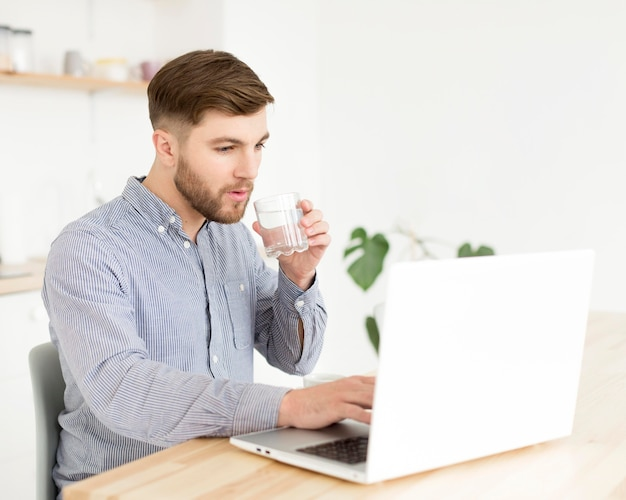 Homem de retrato em casa trabalhando no laptop