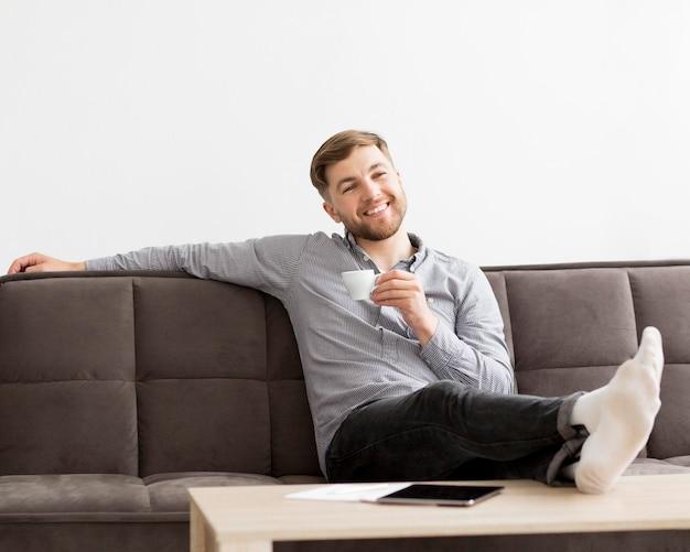 Homem de retrato no sofá bebendo café