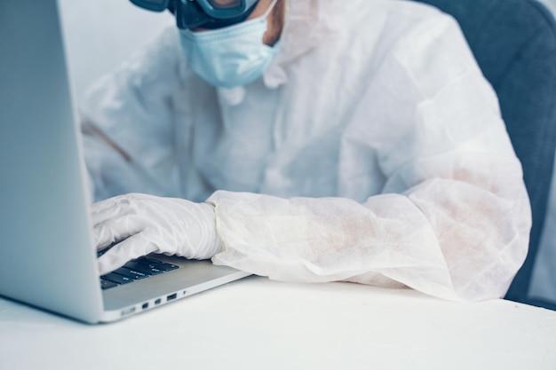 Homem de risco biológico com laptop. mãos nas luvas, usando o laptop.