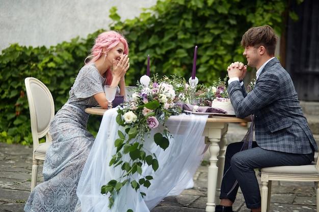 Homem de riso e sua dama de cabelo rosa sentam-se na mesa de jantar com uma decoração rosa