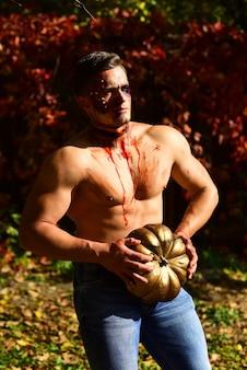 Homem de rosto assustador com horror compõem-se segurando a lanterna de jack de cabeça de abóbora. homem zumbi muscular assustador e sangrento com abóbora ao ar livre. conceito de halloween ou horror - gritando zumbi morto-vivo.