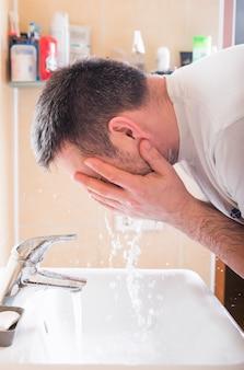 Homem de rosto de lavagem que enxágua o sabão com água corrente na pia, prevenção do corpo de coronavirus higiene.