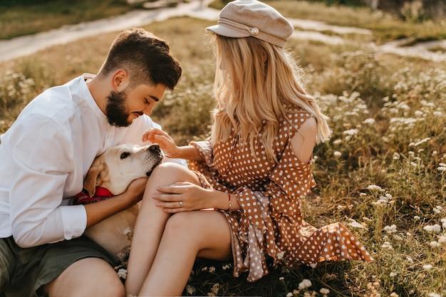 Homem de roupa branca e sua dama de boina estão sentados na grama, acariciando e brincando com o cachorro.