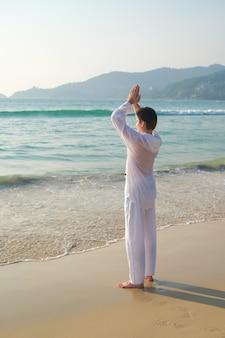 Homem de roupa branca segura as mãos em um gesto de oração e pratica ioga