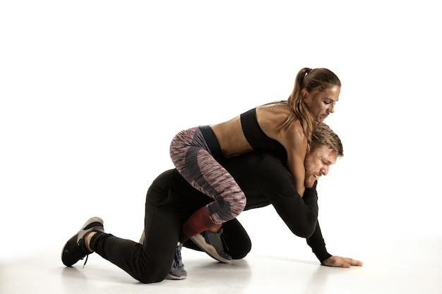 Homem de roupa preta e mulher atlética lutando na parede branca do estúdio