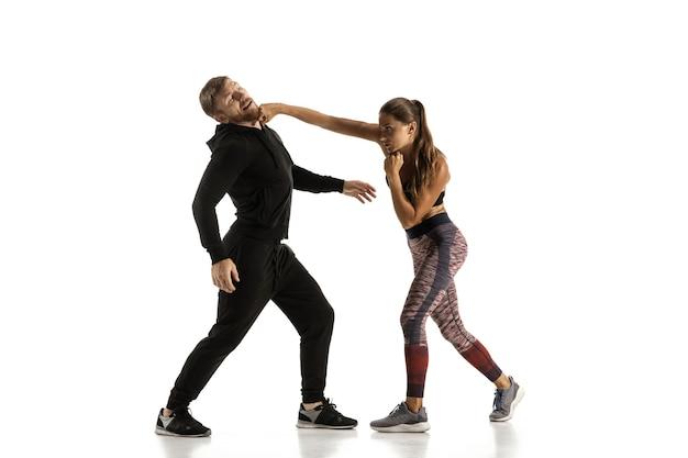 Homem de roupa preta e mulher atlética lutando na parede branca do estúdio Foto gratuita