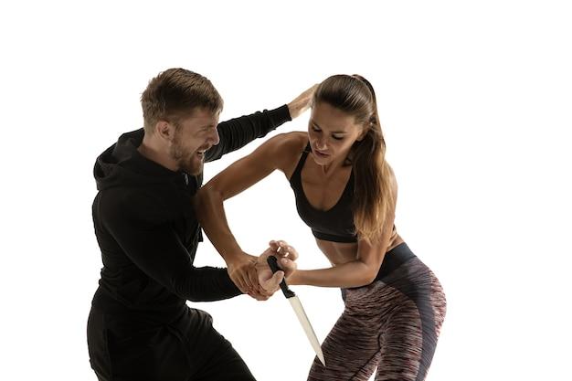Homem de roupa preta e mulher caucasiana atlética lutando no fundo branco do estúdio. autodefesa das mulheres, direitos, conceito de igualdade. enfrentando a violência doméstica ou roubo na rua.