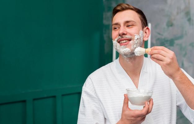 Homem de roupão aplicando espuma de barbear no rosto com espaço de cópia