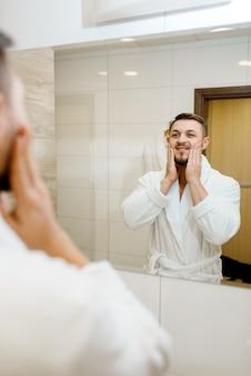 Homem de roupão esfrega loção pós-barba no rosto no espelho do banheiro, rotina de higiene matinal.