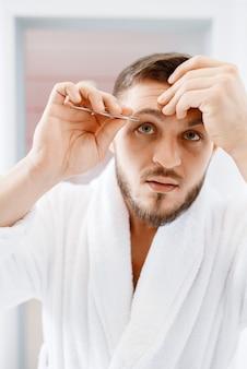 Homem de roupão remove pelos da sobrancelha no banheiro, higiene matinal de rotina.