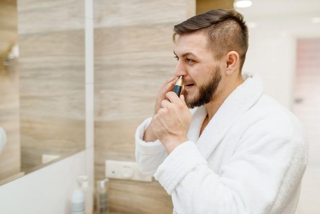 Homem de roupão remove pelos do nariz no banheiro, higiene matinal de rotina.