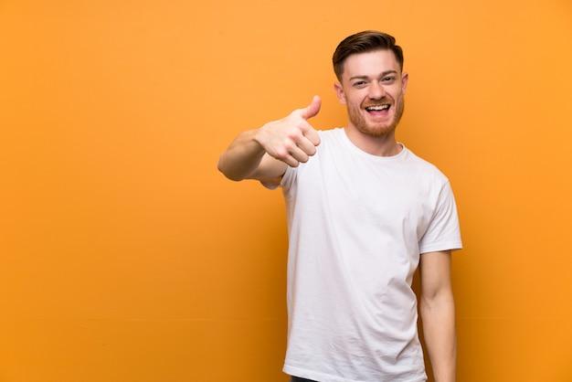 Homem de ruiva ao longo da parede marrom com polegares para cima porque algo bom aconteceu
