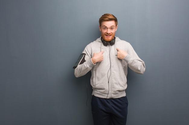 Homem de ruiva jovem fitness surpreendido, sente-se bem sucedido e próspero