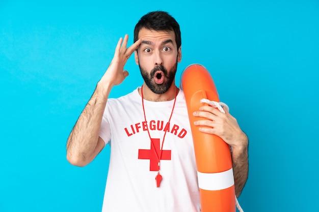 Homem de salva-vidas sobre parede azul isolada acaba de perceber algo e pretende a solução