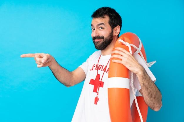Homem de salva-vidas sobre parede azul isolada, apontando o dedo para o lado e apresentando um produto