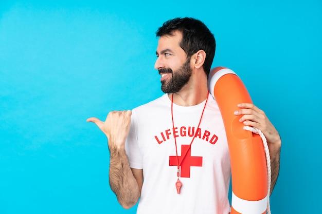 Homem de salva-vidas sobre parede azul isolada, apontando para o lado para apresentar um produto