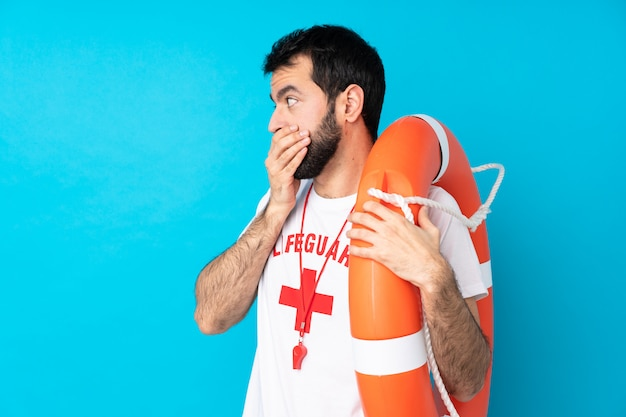 Homem de salva-vidas sobre parede azul isolada, cobrindo a boca e olhando para o lado