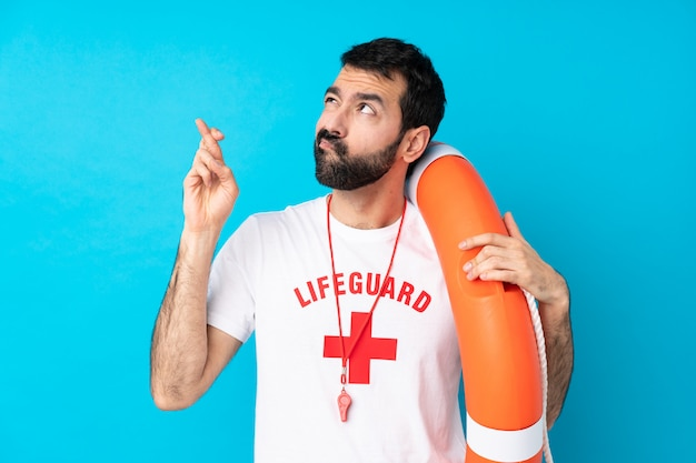 Homem de salva-vidas sobre parede azul isolada com dedos cruzando e desejando o melhor