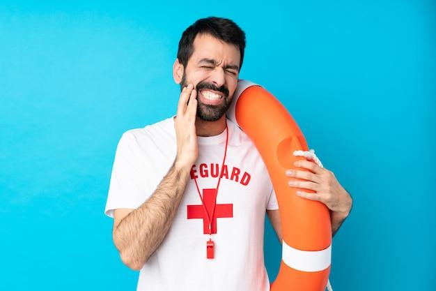 Homem de salva-vidas sobre parede azul isolada com dor de dente