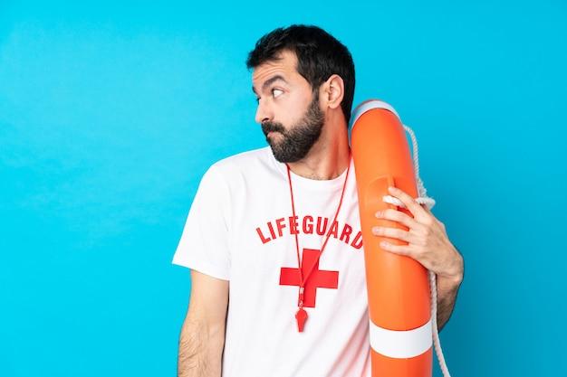 Homem de salva-vidas sobre parede azul isolada, fazendo dúvidas gesto olhando de lado