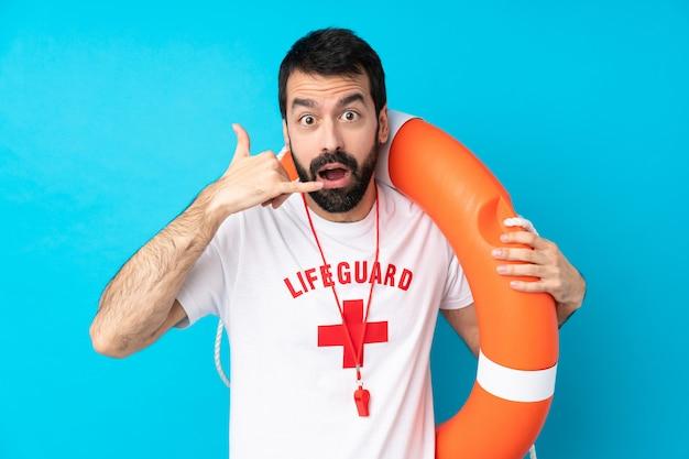 Homem de salva-vidas sobre parede azul isolada, fazendo gesto de telefone e duvidar