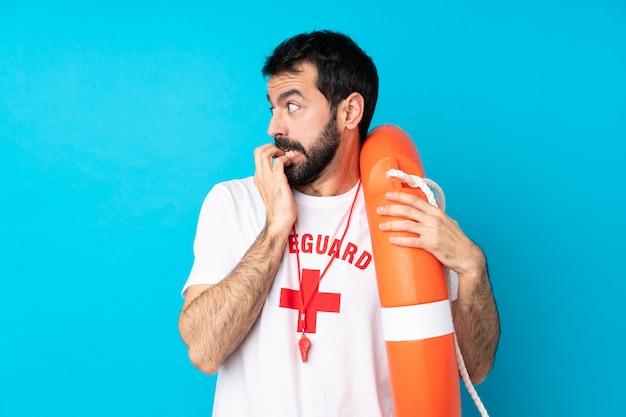 Homem de salva-vidas sobre parede azul isolada, nervoso e assustado, colocando as mãos na boca